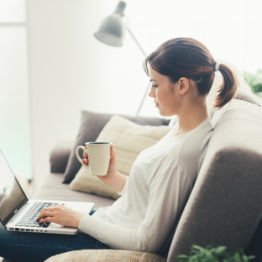 Young woman relaxing at home on the couch, she is having a coffee and using a laptop